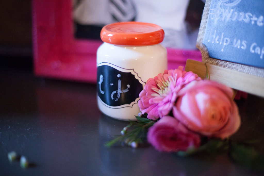 white mason jar with orange lid with the initials of the couple and floral provided by The English Garden Raleigh
