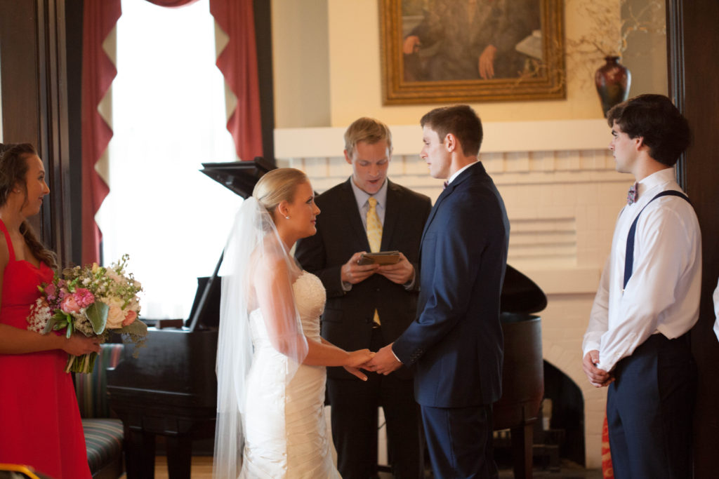 ceremony photo of the bride and groom exchanging vows inside The Tucker House in downtown Raleigh