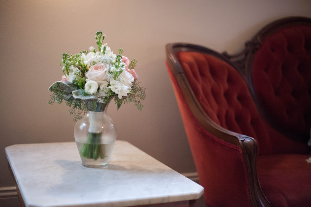 picture of bridal bouquet made by The English Garden Raleigh on a side table next to a piece of red vintage furniture