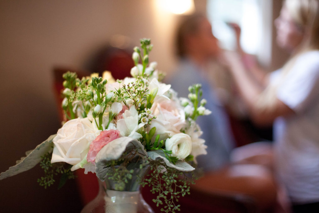 Bridal bouquet made by The English Garden Raleigh in fore ground with bride getting her makeup done in the background