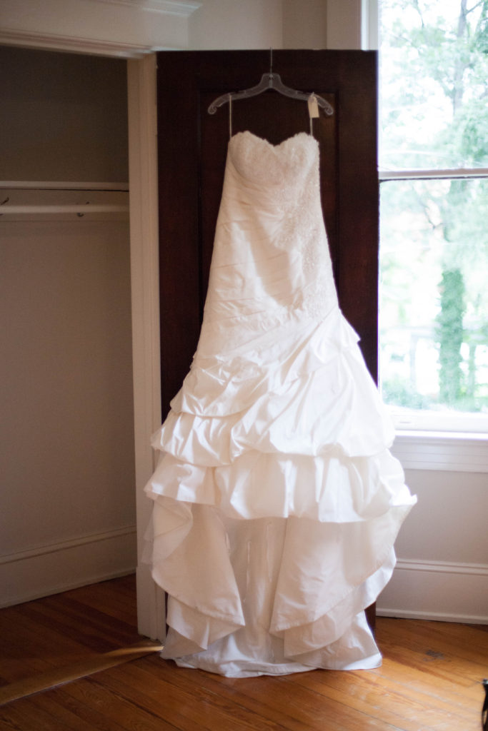 picture of bridal gown hanging on the top of a wooden door at The Tucker House in downtown Raleigh