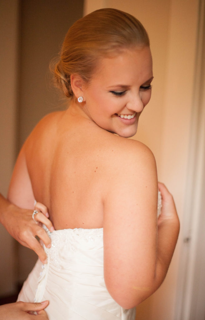 bride getting zipped into her dress while smiling at The Tucker House in downtown Raleigh