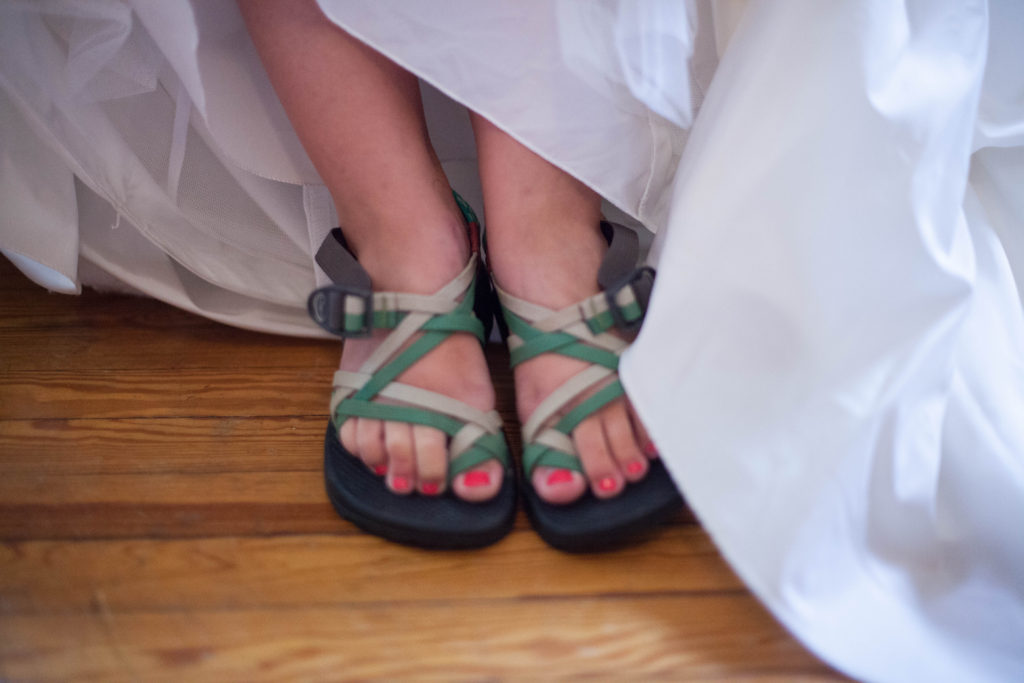 bride wearing chacos under her wedding dress