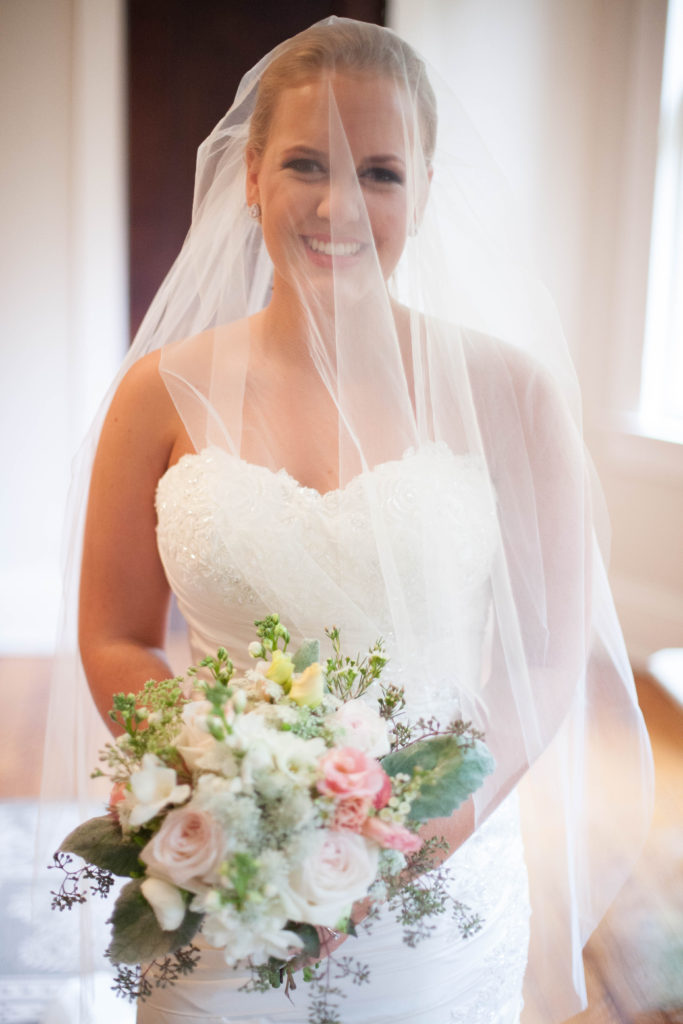 bride with blusher over face holding her textural bouquet made by The English Garden Raleigh