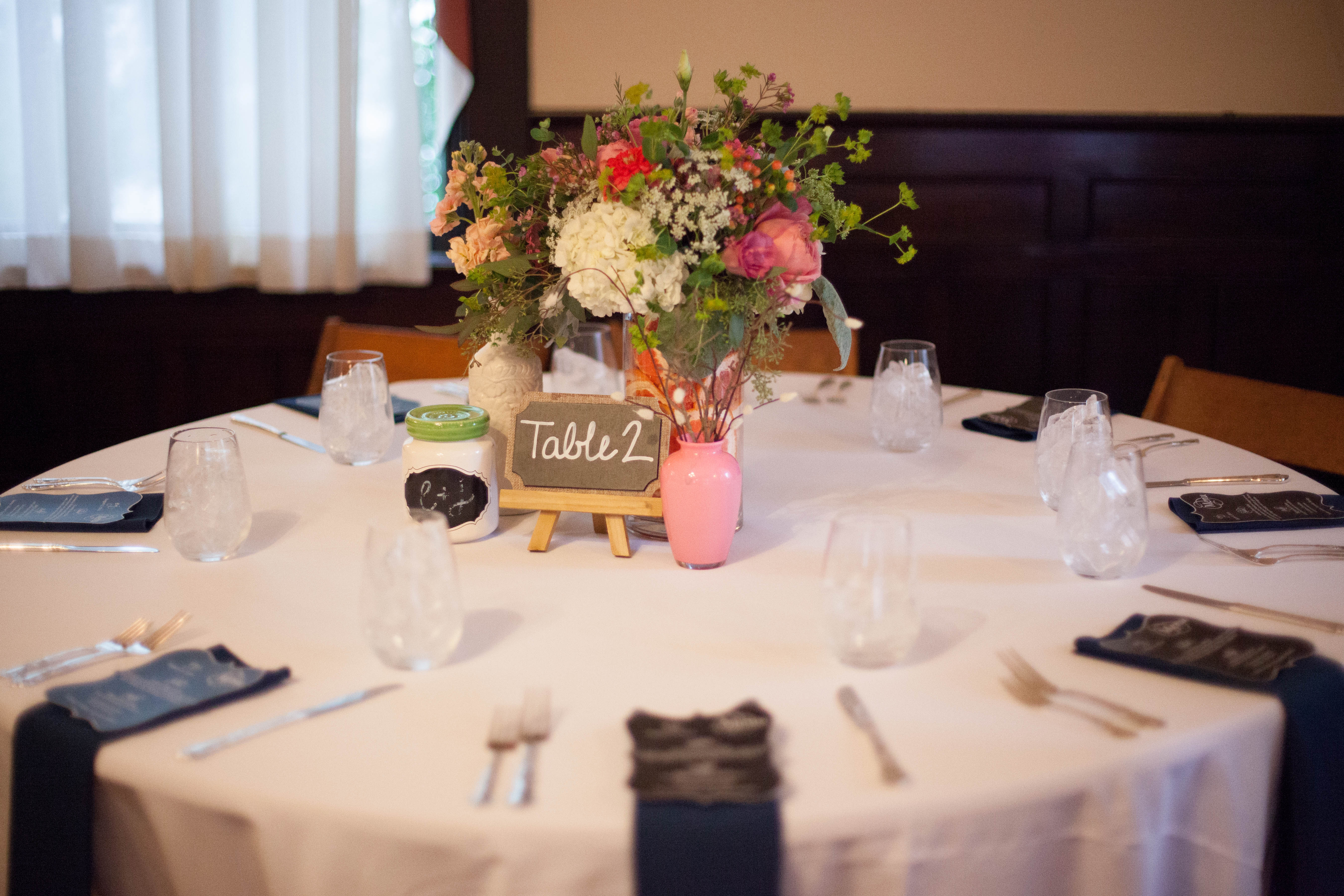 round guest table and white cotton linen with florals in painted bud vases from The English Garden Raleigh and table number on chalkboard with navy napkins and menu cards