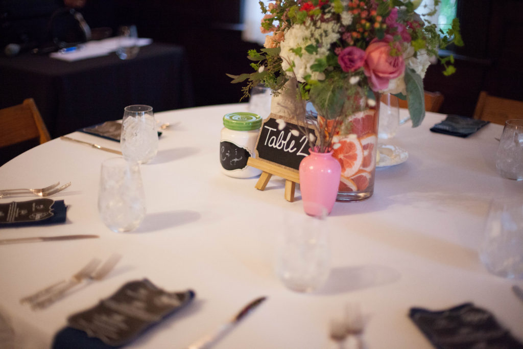 round guest table with citrus and floral centerpiece by The English Garden Raleigh and menu cards as well as table numbers on chalkboards