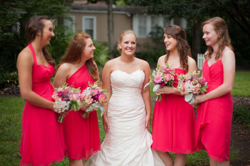 bridesmaids looking at smiling bride