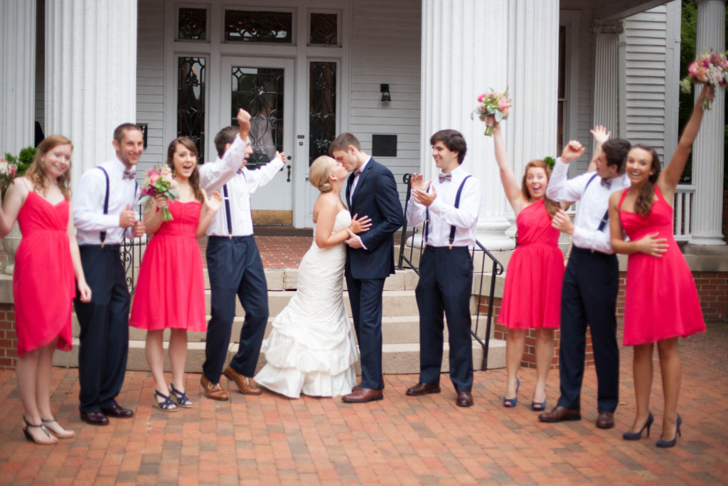 cheering bridal party with couple kissing in the center
