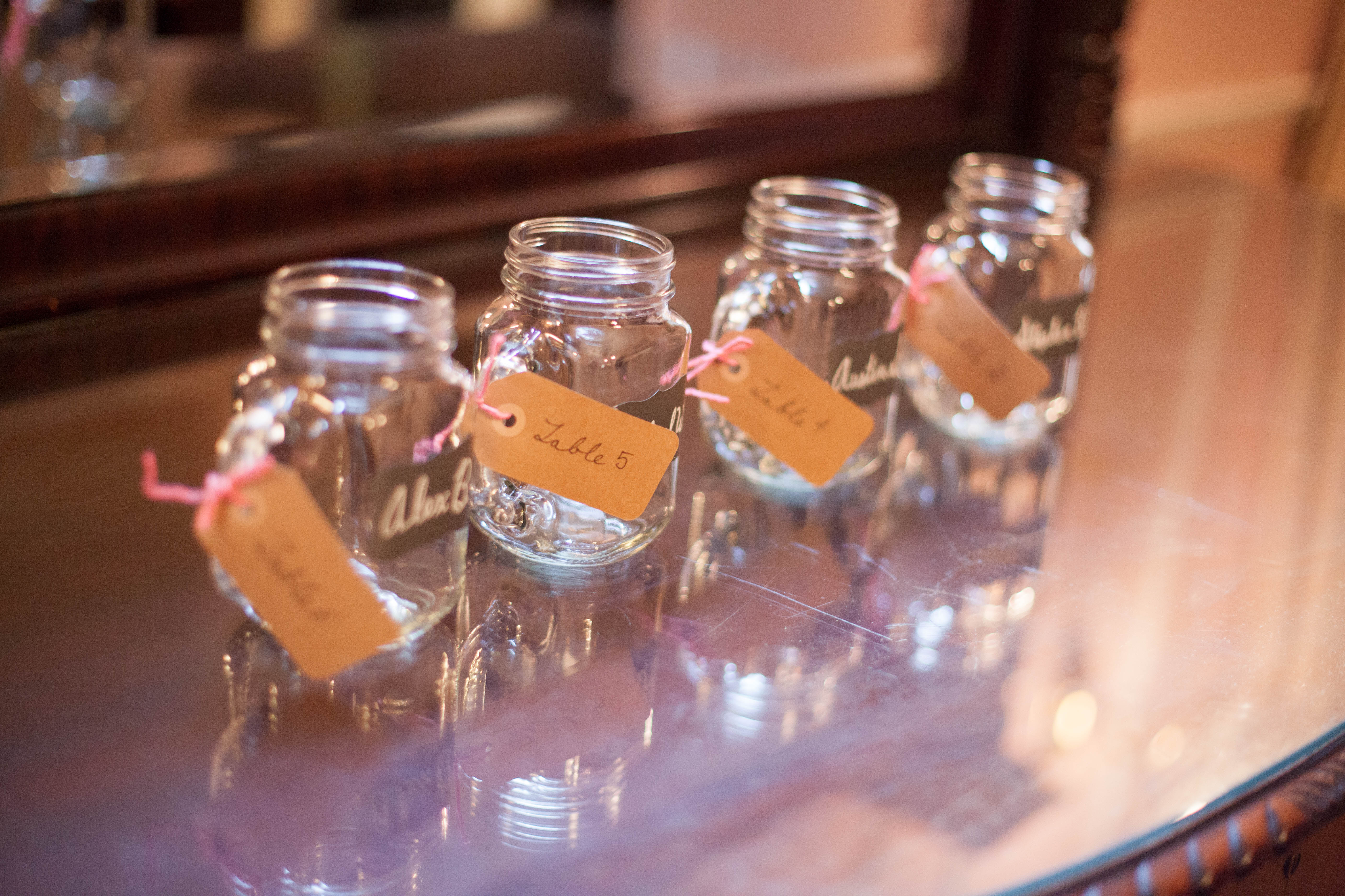 DIY Wedding project, escort cards with tables number tied to clear mason jars with handles with chalkboard label of guests name used as escort cards