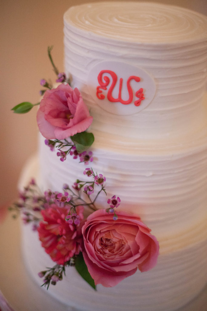 3 tiered white wedding cake decorate by flowers and couples monogram