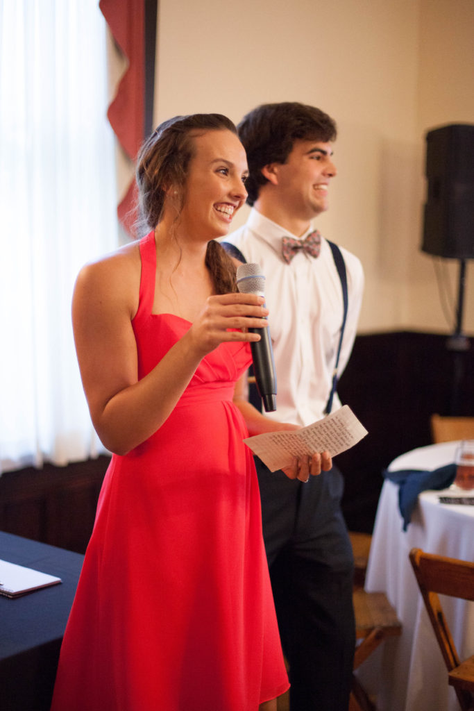 maid of honor giving her speech at The Tucker House in downtown Raleigh in coral bridesmaids dress from Maggie Bridal