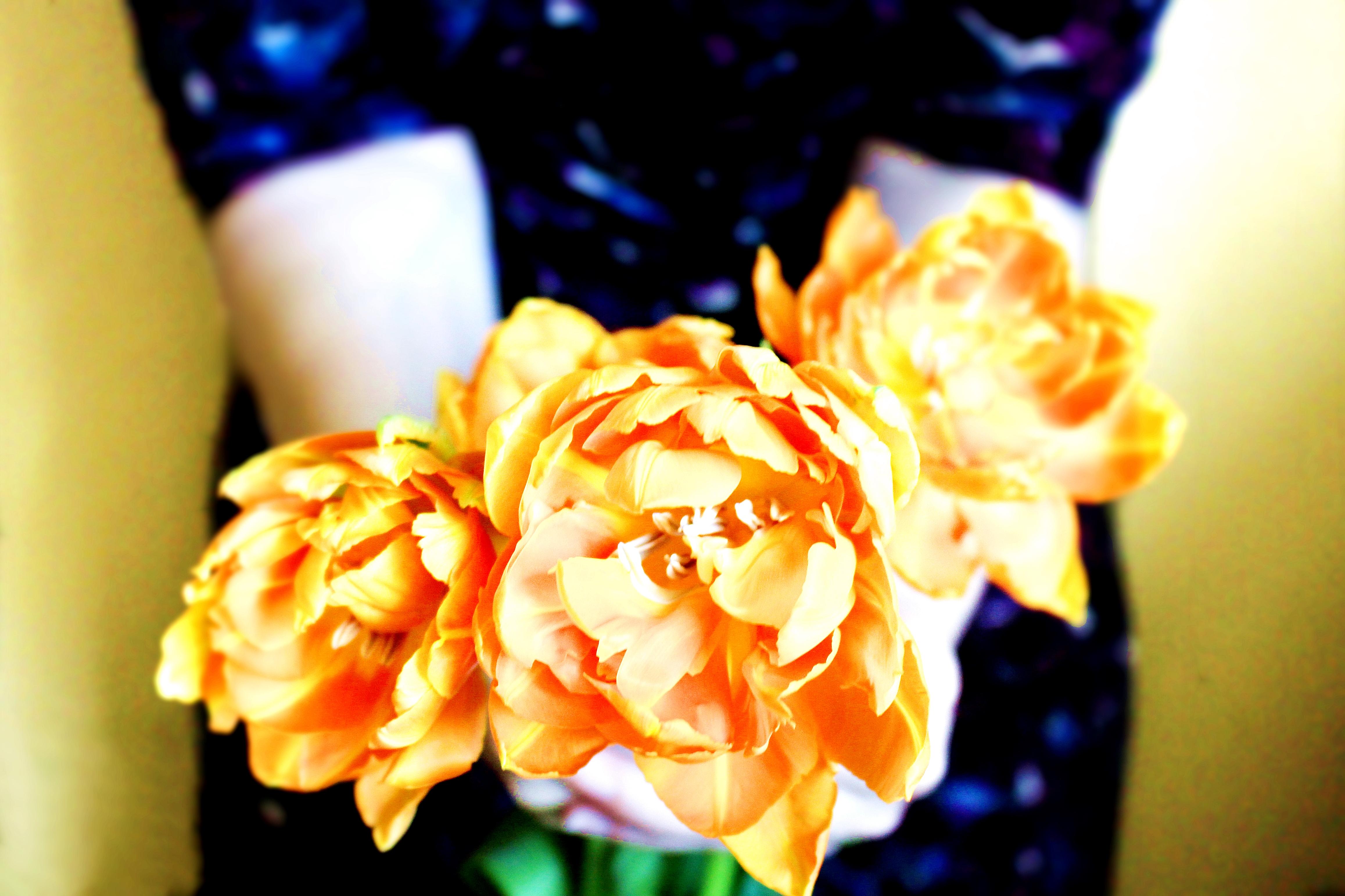 wedding trends bright orange flowers held by girl in sparkly navy sequin dress