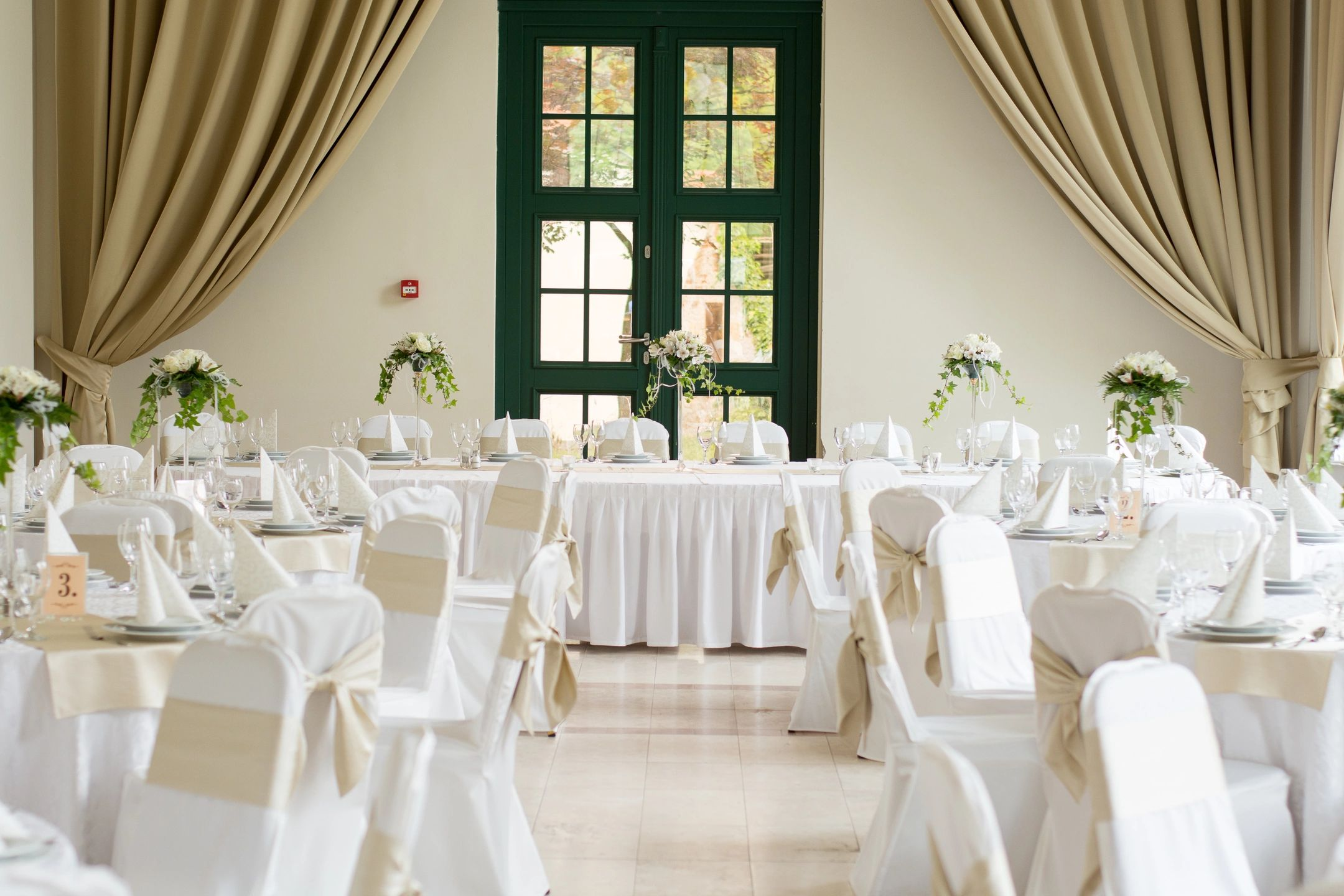 wedding reception room white and beige neutral with greenery centerpieces draping and green french doors
