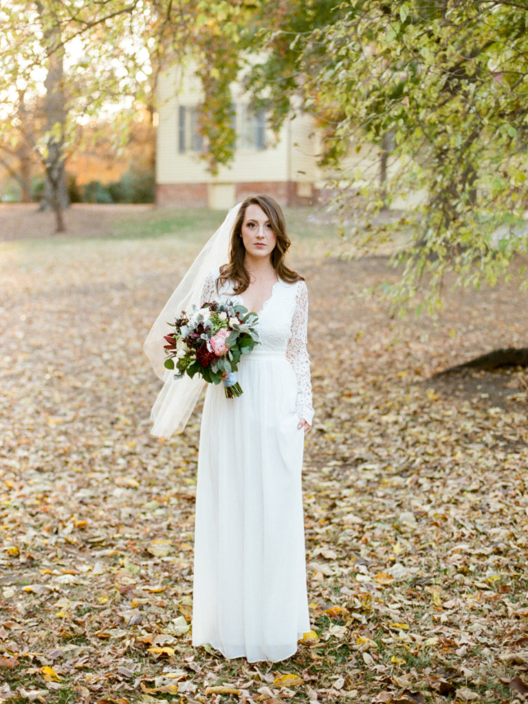 bride in full length wedding dress with lace sleeves burgundy pink and white bridal bouquet by The English Garden Raleigh photo by Live View Studios