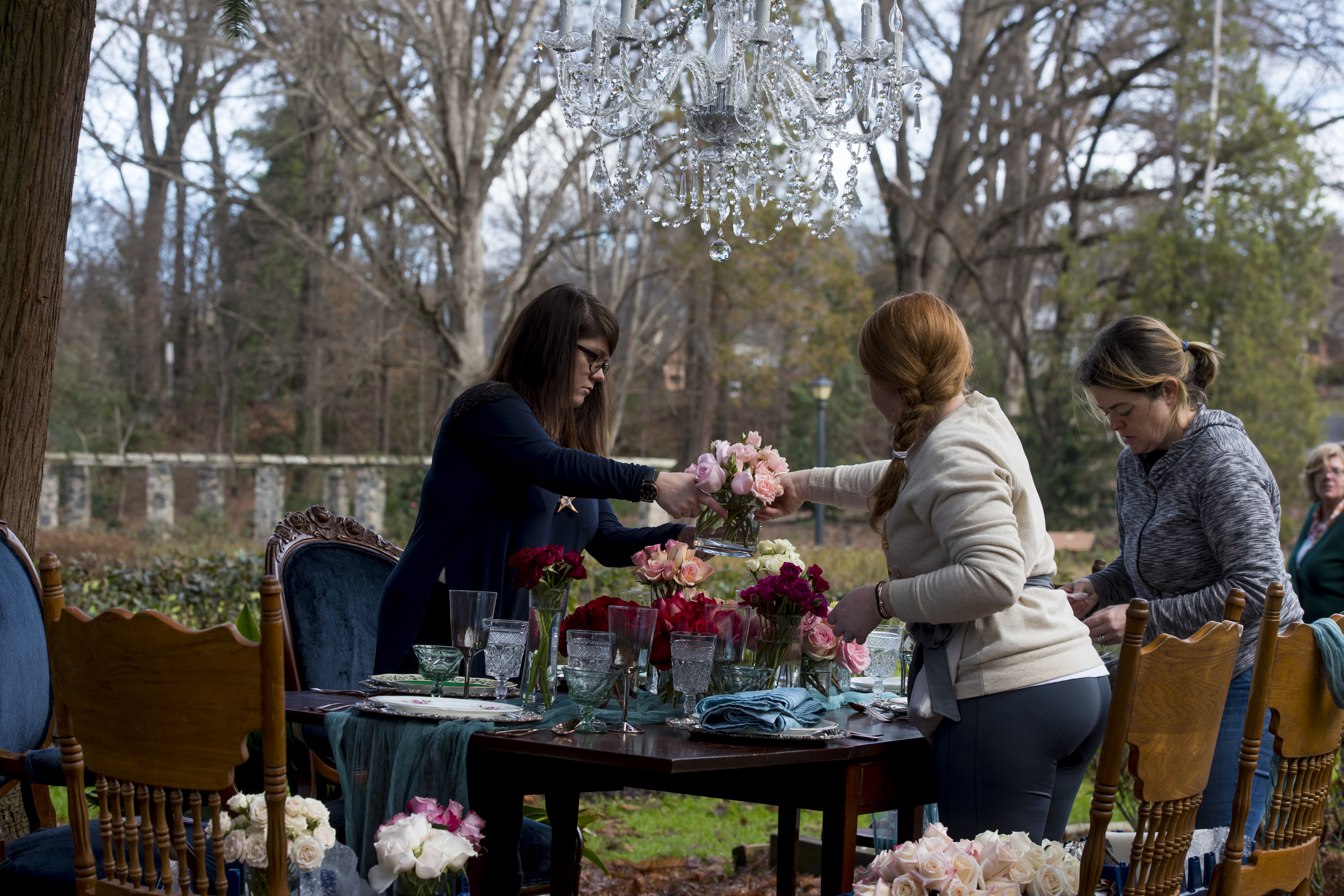 setting up a table with floral centerpieces for a styled shoot