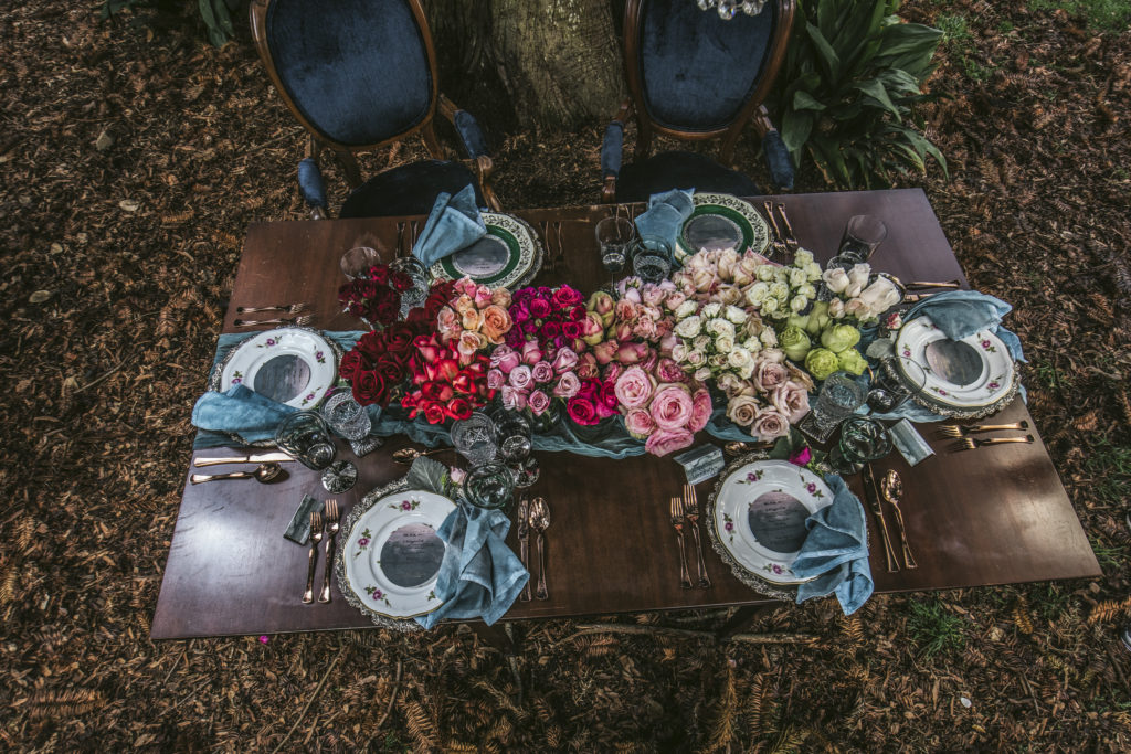 dark wood sweetheart table with rose floral centerpieces and navy blue royal bride and groom vintage chairs under a tree with vintage plates from The Prettiest Pieces photo by Nieto Photography