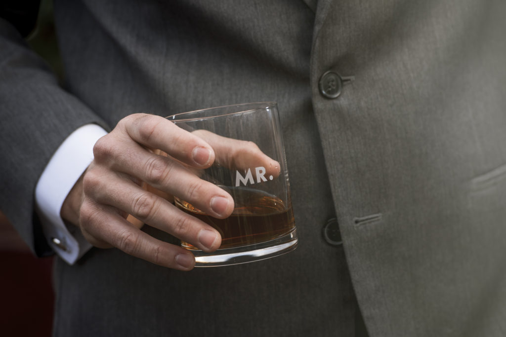 groom holding mr and mrs kate spade rocks glass photo by Nieto Photography