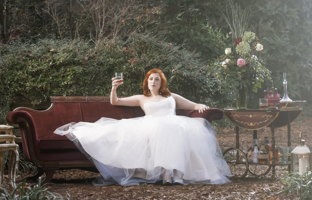 bride on red velvet couch from The Prettiest Pieces photo by Nieto Photography