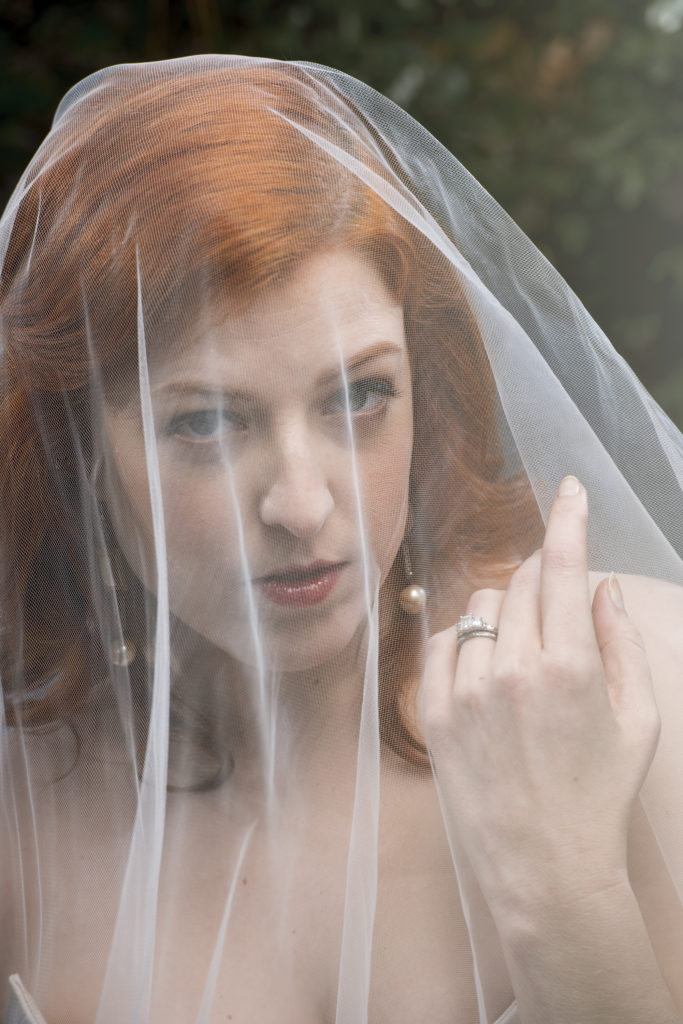 red head bride with veil over face blusher photo by Nieto Photography