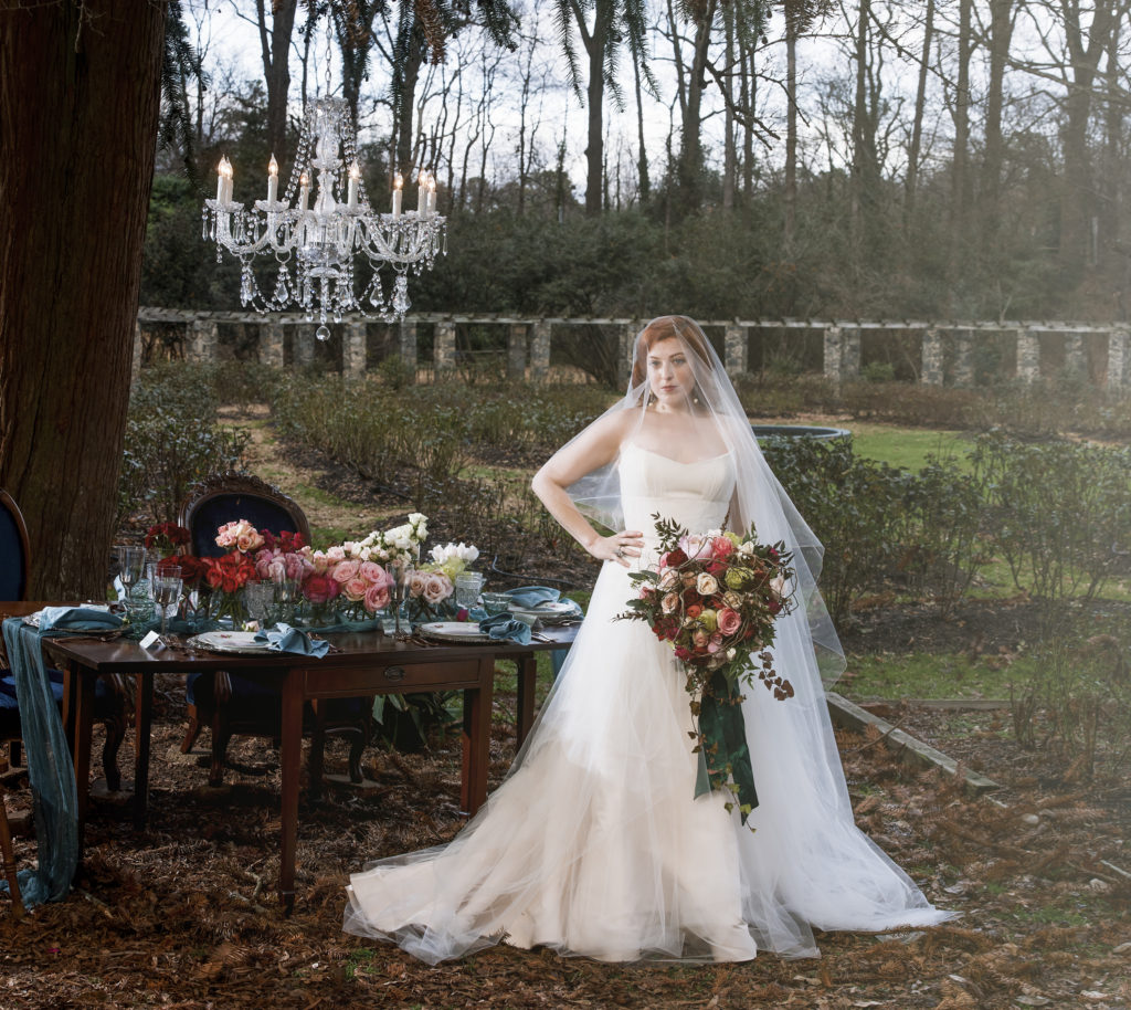 redhead bride holding bridal bouquet by The English Garden standing in front of sweetheart table provided by The Prettiest Pieces with glass chandelier from Get Lit Special Event Lighting photo by Nieto Photography photo by Nieto Photography