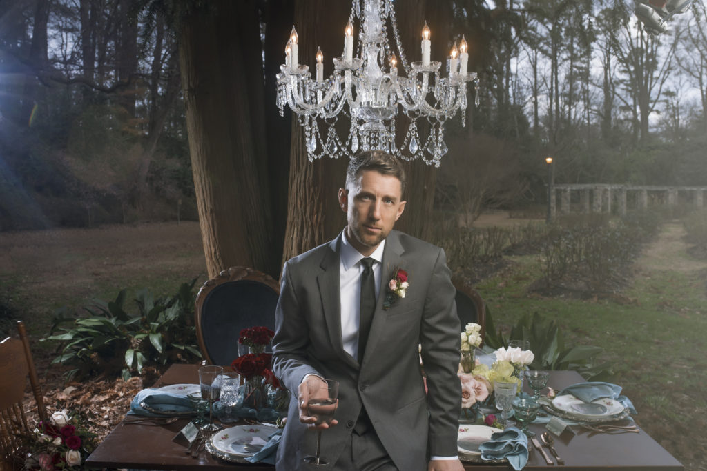 groom holding mr and mrs kate spade rocks glass in front of sweetheart table provided by The Prettiest Pieces with chandelier from Git Lit Special Event Lighting in The Raleigh Rose Garden photo by Nieto Photography