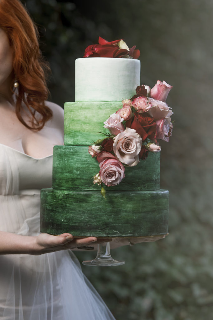 redhead bride holding four tiered green watercolor wedding cake photo by Nieto Photography