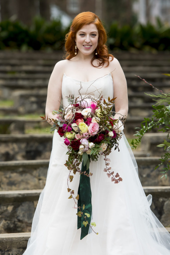redhead bride holding bridal bouquet by the english garden raleigh in the raleigh rose garden photo by Nieto Photography