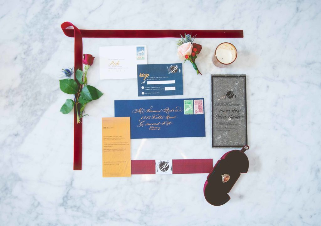 wedding invitation flatlay navy and burgundy on marble background